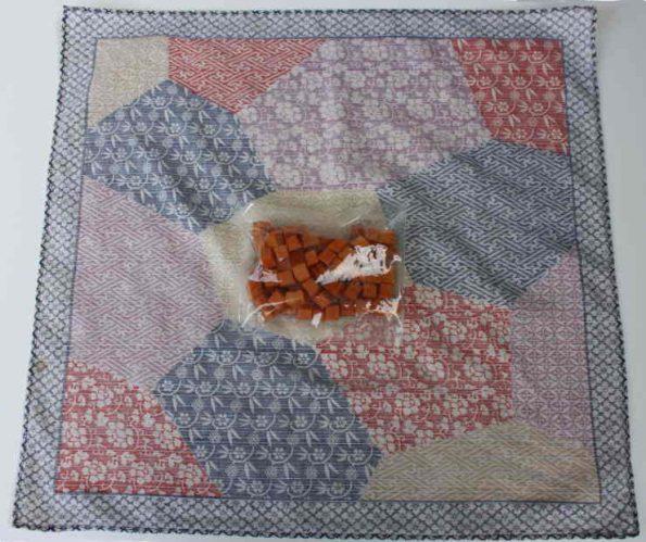 Breitet ein Furoshiki oder Nickytuch aus und legt das Geschenk in die Mitte